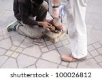 Poor shoe shiner - stock photo