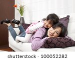 Woman and young girl lying in sofa smiling - stock photo