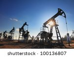 working oil pumps silhouette against sun - stock photo
