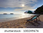 wood chairs bed and umbrella on sand beach at sun set time - stock photo