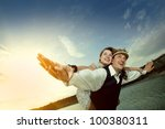 Happy couple enjoying flying over the sea, female on man's back - stock photo