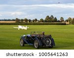 Small photo of Old Warden Aerodrome, Biggleswade, Bedfordshire, UK AUGUST 19 2017 - An MG TA sits on the airstrip onlooking as a DeHavilland Comet comes in on approach over a white aircraft on the ground.