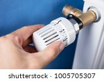 Small photo of Person's Hand Adjusting Temperature On Thermostat To Control Heat In Central Heating System