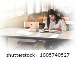 woman reading book on desk...   Shutterstock . vector #1005740527