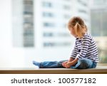 Adorable little girl sitting by the window - stock photo