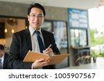asian businessman holding a... | Shutterstock . vector #1005907567
