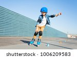 boy learning to roller skate on ... | Shutterstock . vector #1006209583