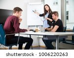 Small photo of Businesswoman Giving Presentation While Using Laptop With Collea