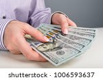 hands counting dollar banknotes | Shutterstock . vector #1006593637