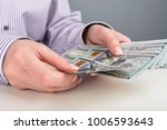 hands counting dollar banknotes | Shutterstock . vector #1006593643