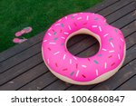 Small photo of The inflatable circle in the form of a donut lies on a wooden pier. next to it lie the shale on the lawn. Summer, beach season.