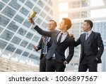 Small photo of Businessmen appreciate the trophy.