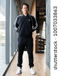 Small photo of BANGKOK, THAILAND - DECEMBER 21, 2018 :A man wearing new collction adidas original jacket and sweatpants, A German multinational corporation that designs and manufactures sports shoes, clothing