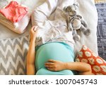 pregnant woman is packing baby... | Shutterstock . vector #1007045743