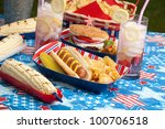 Hot dogs, corn and burgers on 4th of July picnic in patriotic theme - stock photo