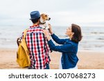 Small photo of Young female and male tourists have walk near sea, carry their favourite pet, enjoy nice weather. Unrecognizable young male in checkered shirt carries bag and dog on hands, stands back at camera