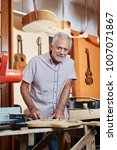 Small photo of Senior citizen as luthier master makes new guitar at workshop
