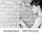 guy measures brick wall with... | Shutterstock . vector #1007241313