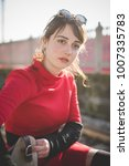 Small photo of portrait red dressed young beautiful woman posing outdoor back light looking away smiling - positive emotions, happiness, carefree concept
