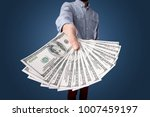 Small photo of Young businessman holding large amount of bills