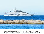 Small photo of Daylight close-up view to white yacht cruising on water and splitting rocks. Bright blue clear sky. Negative copy space, place for text. Cap d'Ail, france