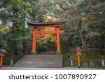 Stock photo a giant torii gate stands in an autumn forest at the entrance to the usa shrine a famous shinto 1007890927