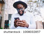 Small photo of Emotional surprised african american guy with low prices in web store receiving message with promo code,excited dark skinned hipster guy in trendy hat overjoyed with winning online contest on web site