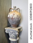 Small photo of Ancient Greek amphora on the pedestal of the Corinthian column