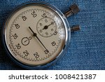 Small photo of Stopwatch, on worn blue denim background, value measure time, old clock arrow minute and second accuracy timer record