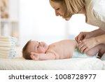 mother putting diaper on her... | Shutterstock . vector #1008728977