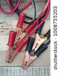 Small photo of booster jumper cable for car battery on wooden background.