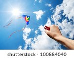 kite flying in a beautiful sky with sun and clouds - stock photo