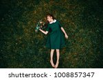 Young girl with red hairlying on ground. Portrait from above of cute teenager female relaxing on grass in summer. Lovely skinny female in beautiful stylish dress holding bouquet of flowers in hand.