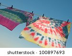 Two tie-dyed t-shirts hanging on clothes line and blowing in the wind, against blue sky - stock photo