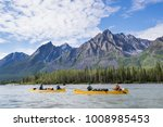 Group paddling down the whitewater of the Nahanni River in the Northwest Territories.