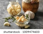 Small photo of Preserved garlic in glass bowl on table