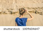 a woman looks at the sand....   Shutterstock . vector #1009604647