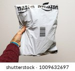 Small photo of PARIS, FRANCE - JAN 23, 2018: Man holding against white background a plastic parcel delivery of Amazon package containing clothes or shoes