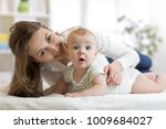 mom and her little son on bed.... | Shutterstock . vector #1009684027