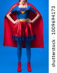 Small photo of partial view of woman in superhero costume standing akimbo isolated on blue
