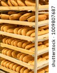 Small photo of shelves with fresh bread and white bread in the mall on pallets