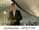 Elegant young businessman using his PC tablet while walking - stock photo
