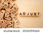 Small photo of Adjust word cube on wood background