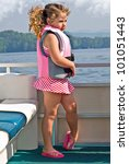 A girl in a pink life jacket standing on the front of a pontoon boat. - stock photo