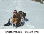 Woman in snow with dogs - stock photo