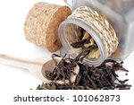 Small photo of Tea leaves in transparent parison with wooden spoon isolated on white background