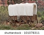 Nice old covered wagon in Arizona, red rock background - stock photo