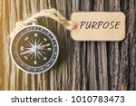 Small photo of PURPOSE text written on paper tag with magnetic compass on old wooden background. A concept.