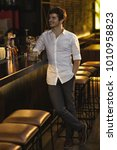 Small photo of Full length vertical portrait of a cheerful handsome young man smiling happily enjoying drinking whiskey at the bar macho bachelor emotions lifestyle happiness event festive celebrating confidence