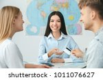 young couple in a tour agency... | Shutterstock . vector #1011076627